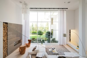 Efekt vzdušnosti prostoru vychází nejen z jeho otevření do horního patra. Je totiž také výsledkem velkorysého prosklení fasády. Okna, ať už rovná či zaoblená, vpouštějí dovnitř spoustu světla a umožňují optické propojení s upravenou zahradou.
