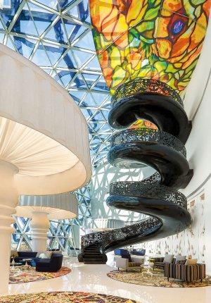 Impozantní, na míru navržené čtyřúrovňové točité schodiště působí díky nenápadnému postrannímu kotvení do stěn, jako by v prostoru lobby levitovalo. Lemované dekorativním zábradlím s orientálními ornamenty vede hosty až k výhledové plošině hotelu. Charismatický prostor atria pod prosklenou fasádou doplňují vedle rozměrné vitráže také obrovské lampy.