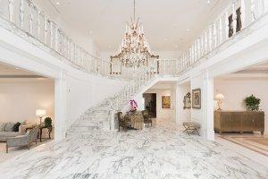 Obklad bílým thassoským mramorem přidává vstupní hale s impozantním schodištěm a křišťálovým lustrem na velkoleposti. Otevřená dispozice umožňuje přímý vstup do formální jídelny (vpravo) a obývacího pokoje (vlevo).