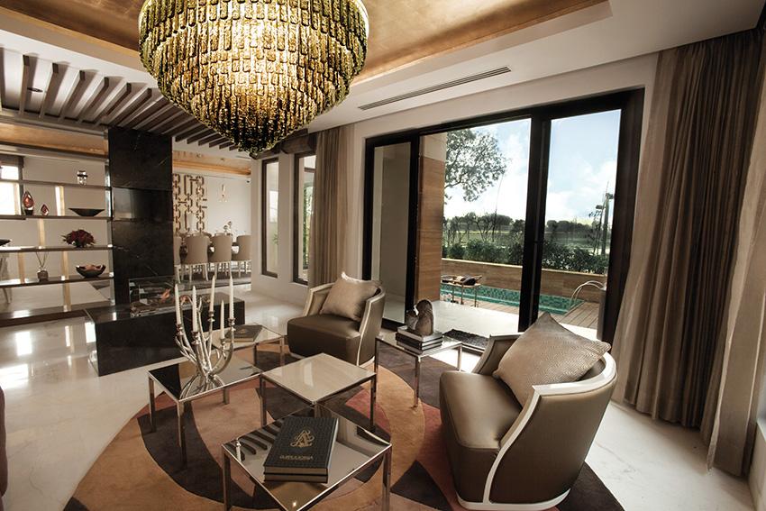 Společenskému obytnému prostoru dominuje impozantní stropní svítidlo Plafoniera od Aldebaran, návrh Samuele Mazza. Lustr s výškou 63 cm a 12 žárovkami tvoří obdélníkové prvky z kouřového muránského skla, zavěšené na kruhové konstrukci z kovu ve zlaté povrchové úpravě.
