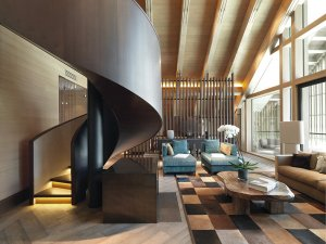 """Nezanedbatelný podíl dřeva v interiéru zahrnuje nejen obklady podlah, stěn i stropů, ale také některý nábytek. Dominantou interiéru společenské zóny je sice impozantní kovová """"stuha"""" točitého schodiště s podsvětlenými stupni a plným zábradlím, ale neméně efektní je rovněž konferenční stolek z masivního, hrubě opracovaného dřeva."""